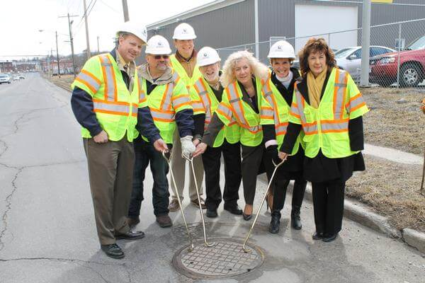 National Water Main Cleaning team after ribbon cutting ceremony opening manhole cover